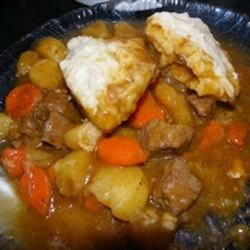 Mom's Hearty Beef Stew with Dumplings Recipe - Tender chunks of beef simmer for hours in a rich gravy with carrots and potatoes, then are topped with homemade dumplings. It's a flavorful, hearty meal for a cold night.