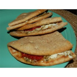 Warm Goat Cheese Sandwiches Recipe - Basil pesto, sun-dried tomatoes and goat cheese intermingle to produce a savory, colorful, EASY vegetarian sandwich. Wonderful served with seedless purple grapes.