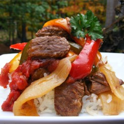 Slow-Cooker Pepper Steak Recipe - Tasty strips of sirloin are seasoned with garlic powder, then slow cooked with onion, green pepper, and stewed tomatoes for this easy and comforting dinner.