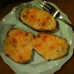 Twice Baked Cheesy Potatoes Recipe - In this recipe, sour cream, butter and American cheese are whipped into baked russet potato pulp, then re-baked the potato skins.