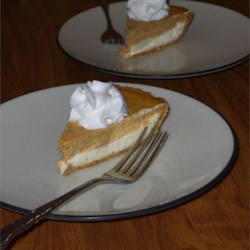 Pumpkin Layer Cheesecake Recipe - This cheesecake makes a dramatic presentation with its two layers of white and pumpkin. It's easy to make, too, by using a prepared graham cracker crust.