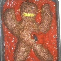 "Halloween Halfling Meatloaf Recipe - A Halloween meatloaf is decorated like a spooky Halfling -- a mysterious humanoid creature with yellow corn teeth, green pepper ears, black olive eyeballs, and a background of scary ""blood"" ketchup."