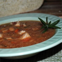 Rosemary Chicken Stew Recipe - This hearty stew slowly simmers bite-size chicken pieces with onions, mushrooms, tomatoes, garlic, rosemary, and great northern beans. It's great on a cold night paired with homemade biscuits.