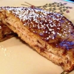 Cinnamon Raisin Stuffed French Toast Recipe - Cinnamon cream cheese is spread between slices of raisin bread, dipped in egg, and pan-fried to make an easy but special breakfast treat.