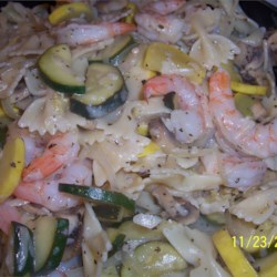 Shrimp with Penne and Squash Recipe - Fresh yellow squash and zucchini cook in olive oil with shrimp, garlic, herbs, and lemon juice. Served over hot penne pasta with chives and Parmesan cheese.