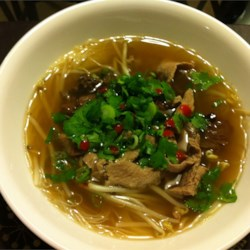 Beef Pho Recipe and Video - Authentic South Vietnamese Style Pho. A comforting richly seasoned beef broth is ladled over rice noodles and thinly sliced beef. Add hot sauce and plum sauce to taste and top with cilantro, basil, lime juice and bean sprouts.