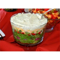 Seven Layer Salad Recipe - A glass salad bowl is a must, otherwise your diner guests will miss all the pretty layers. Those layers begin with chopped lettuce and go on from there  - onion, peas, shredded cheese, bacon, cauliflower, and finally a creamy parmesan and mayonnaise dressing.