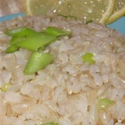 Out of the Hat Rice Recipe - A pretty side dish of lemon-flavored basmati rice and chopped green onions served in round scoops on fresh spinach leaves.