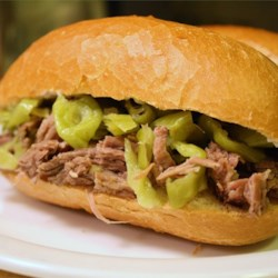 Pepperoncini Beef Recipe - Roast beef cooked in a slow cooker with garlic and pepperoncini makes a delicious and simple filling for sandwiches. Serve on hoagie rolls with provolone or mozzarella cheese and your favorite condiments.