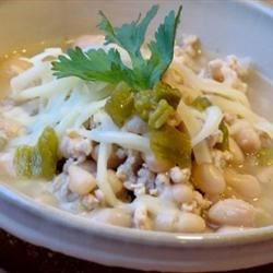 White Chili with Ground Turkey Recipe - Browned ground turkey and cannellini beans are combined with green chilies, onion and garlic in this chicken stock based soup seasoned with cumin, oregano and cinnamon.  Serve with grated jack cheese.