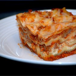 Easy Lasagna I Recipe - Mushrooms, onions and ground beef in a ready-made pasta sauce are layered with cottage cheese, ricotta cheese and Parmesan between uncooked lasagna noodles. Sprinkle mozzarella over the top and bake. It's that simple!