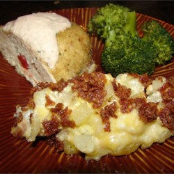 Hash Brown Casserole I Recipe - Frozen hash brown potatoes are combined with cream of chicken soup, sour cream, onion and cheddar cheese in this casserole with a buttery cracker crust.