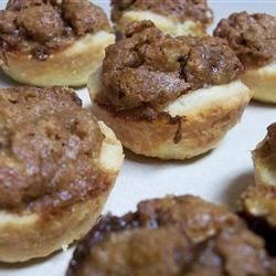 Pecan Cups Recipe -  These miniature pies are made in muffin tins. First, a lovely cream cheese pastry is patted into the bottom of each paper muffin cup. Then filling is whipped up with brown sugar, butter, an egg, and chopped pecans, and dropped by spoonfuls into each muffin cup. Bake and top each mini pie with a dollop of whipped cream.