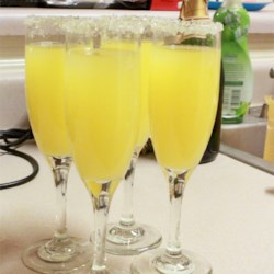 Holiday Mimosa Recipe - Serve up these festive champagne and orange juice classics in glasses rimmed with orange liqueur and sugar.