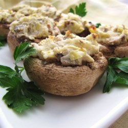 Artichoke Stuffed Mushrooms Recipe - This recipe will deliver tasty mushrooms stuffed with cheese, onion, and artichoke hearts.