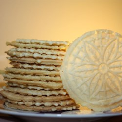 Pizzelles III Recipe and Video - This recipe calls for a batter-like dough and is baked on a pizzelle iron. Powdered sugar adds an elegant touch. In the Italian version, vanilla is replaced by anise. Chocolate may also be used.