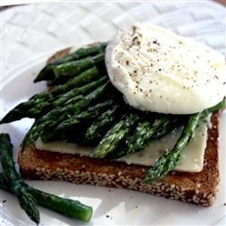 Poached Eggs and Asparagus Recipe - Tender asparagus, poached eggs, and toast make an elegant breakfast for four. Add ham or Canadian bacon, if desired.