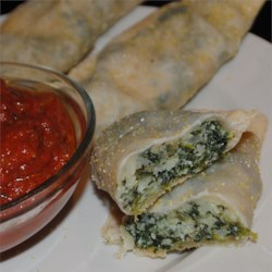 Quick Spinach-Ricotta Calzones Recipe - Go deep this Super Bowl Sunday: Serve calzones. These Italian turnovers are perfect 'finger food' -- no knife and fork required. And because the recipes use refrigerated rolls, it's an easy score. All you have to do is make the fillings.