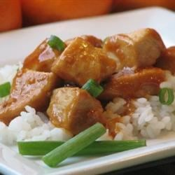 Mama's Asian Chicken and Rice Recipe - Chunks of boneless chicken breast simmer with an Asian-inspired sweet, tangy orange sauce, and are served over hot cooked rice with a sprinkling of green onions.