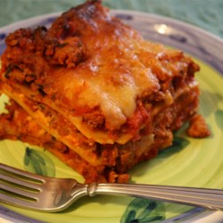 American Lasagna Recipe and Video - Lasagna appeals to the eye as well as to the taste buds. Here, ground beef, onion, garlic, basil, tomatoes and a dash of brown sugar make up the sauce, while ricotta, Parmesan, mozzarella, eggs and parsley are the filling for this layered casserole. Prepare up to 2 days in advance, if desired, and chill covered in the refrigerator until ready to bake. Increase the baking time by about 15 minutes.