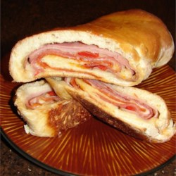 Stromboli Recipe - A pizza with the filling in the middle! Pizza dough is slathered with sauce, then stuffed with ham, sausage, salami, pepperoni, mozzarella cheese, and a few vegetables.