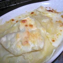 Smoked Salmon Ravioli Recipe - Sheets of fresh pasta are filled with a savory mousse of pureed smoked salmon, eggs, cream, pepper and chives. Serve over a rich and tangy pool of melted gruyere and cream, sprinkle more gruyere over the top, and finish under the broiler.