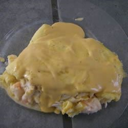 Seafood Omelets with Creamy Cheese Sauce Recipe - Thin, rich omelets are wrapped around a crab and shrimp filling. A luscious Cheddar cheese sauce is draped overtop.