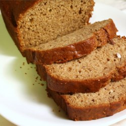 Spiced Applesauce Bread Recipe - Something like a dense version of applesauce spice cake, this moist, quick nut bread is fragrant with apple, cinnamon, nutmeg and allspice.