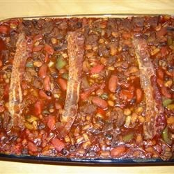 Venison and Barbequed Bean Bake Recipe - Tender pulled venison mingles comfortably with four beans, sweet onions, and barbeque sauce in this filling casserole. It takes some time, but it's worth the effort!