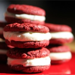 Dawn's Easy Red Velvet Sandwich Cookies Recipe - These tender and tasty cake mix cookies are sure to be a hit when sandwiched with the homemade coconut cream cheese icing and decorated with chopped pecans.