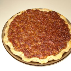 Honey Crunch Pecan Pie Recipe - The cooked pecan filling is made with lots of sugar, eggs and corn syrup, and a bit of vanilla and bourbon. It 's poured into a homemade crust, and topped with luscious pecan halves bathed in brown sugar, butter and honey.