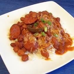 Slow Cooker Pinto Bean Bonanza Recipe - Dry pinto beans simmer for hours with flavorings like bacon, kielbasa sausage, and tomato to make a big pot of goodness. Serve over hot cooked brown rice, and top with cheese and green onion.
