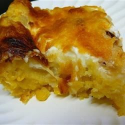 Cheese Corn Casserole Recipe - Corn, sauteed onion, sour cream and grated cheese are combined with a corn muffin base to create this casserole that can be enjoyed alone or as a side to ham or turkey.