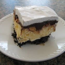 Hot Fudge Sundae Dessert Bars Recipe - A chocolate cookie crust is topped with ice cream, peanuts and fudge sauce before being frozen in this comforting, sweet dessert.