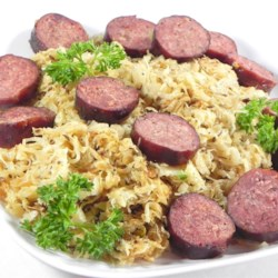 Sausage 'n Kraut Recipe - Your favorite sausage is grilled, then sliced, and served with sauerkraut that's been browned in a buttery spread for a sweet and tangy German-inspired meal.