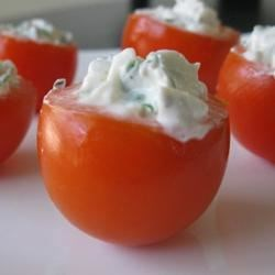 Cherry Tomatoes Filled with Goat Cheese Recipe - A refreshing summertime appetizer, bite-sized cherry tomatoes are filled with a savory mixture of goat cheese and basil.