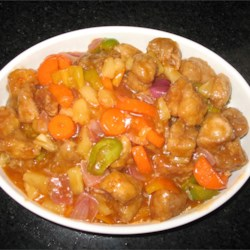 Sweet and Sour Pork I Recipe - This is a very popular dish in Singapore. Crispy fried pork pieces are combined with peppers, tomatoes, pineapple and onion in a spicy sweet and sour sauce.