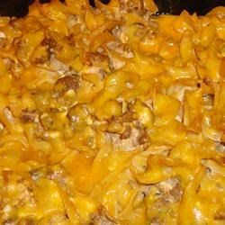 Sour Cream Noodle Bake Recipe - This simple, hearty casserole features ground beef browned in butter and simmered with tomato sauce, garlic salt and pepper. Fold in cottage cheese, sour cream, green onions and egg noodles, then bake with Cheddar cheese sprinkled over the top.