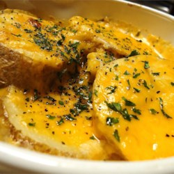 Easy Scalloped Potatoes Recipe - These scalloped potatoes are baked au gratin-style with Cheddar cheese. Always a winner!