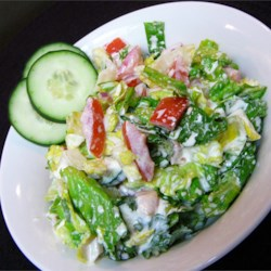 Russian Garden Salad Recipe - This traditional Russian salad coats a mixture of romaine lettuce, tomatoes, cucumber, and onion with sour cream.
