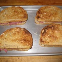 Reuben Sandwich II Recipe - Rye bread filled with sauerkraut, Swiss cheese and corned beef, smothered with a zesty sauce and broiled until golden.