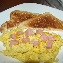 Spam and Eggs Recipe - Cubes of Spam are fried in a skillet with eggs, and topped with cheese.
