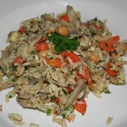 Home-Style Brown Rice Pilaf Recipe - While the brown rice is bubbling on the stove, onions, carrots, garlic, chickpeas, and mushrooms are sauteed in butter until cooked and the flavors are mingled. Eggs are swirled into the pan, the rice is added, and then a nice smattering of parsley and cashews.