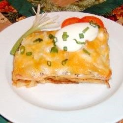 Mexican Lasagna Recipe - Lasagna noodles are baked with an earthy blend of beef, refried beans, oregano, cumin and garlic, with salsa spooned over. Topped with sour cream, green onions, olives and Pepper Jack cheese, the casserole gets one more brief baking to melt the cheese.