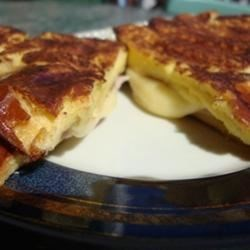 Monte Cristo Sandwiches Recipe - Layered sandwiches featuring ham, turkey and Swiss cheese. These are dipped in egg and browned in a skillet.