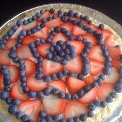 Dessert Pizza Recipe - The crust is made from cookie dough and cooked until golden brown. The topping is a whipped topping and a swirl of fresh fruit slices -kiwi, strawberries or peaches.
