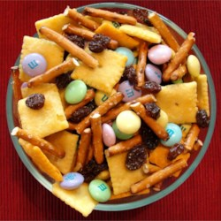 Kids' Party Mix Recipe - This snack mix combines candy coated chocolate pieces, pretzel sticks, Cheddar cheese crackers and raisins.