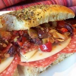 Muffuletta Sandwich Recipe - My Italian family loves this recipe! A crusty loaf of Italian bread is cut in half, and layered with olives, and various meats and cheeses.