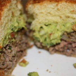 Guacamole Cilantro Lime Cheeseburger Recipe - Melted Monterey Jack cheese lends an added zing to these spiced up hamburgers.  A dollop of fresh guacamole sends it over the top.