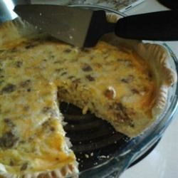 Cheddar Quiche Recipe - The perfect brunch offering, this quiche is packed with the flavors of bacon, hot sauce, Cheddar cheese, eggs, and evaporated milk to make it creamy, thick, and delicious. The crust is made with baking mix, so it is heartier than a flaky pastry. Serve warm or at room temperature.